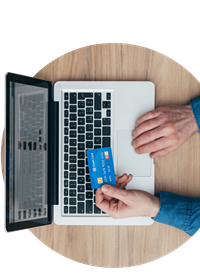 Person on a laptop holding a debit card