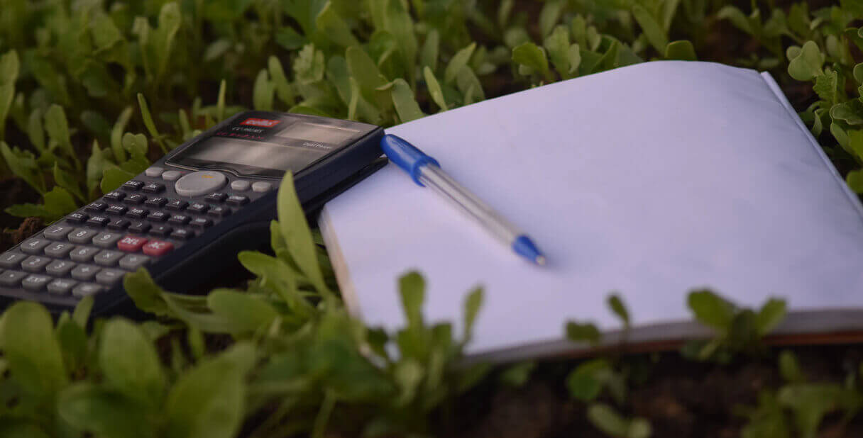 Calculator and notepad lying in grass